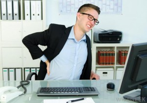 Man sitting at desk in front of a computer holding his sore back as he grimaces in pain