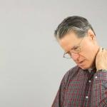 elderly man with glasses rubbing his sore neck