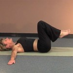 a woman lying on her back on an exercise mat doing back stretches