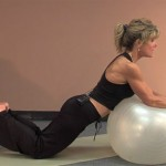 woman in workout clothes using an exercise ball