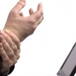 man holding his wrist in front of a computer screen