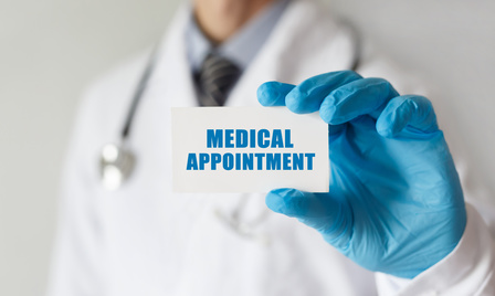 Doctor holding a card that says MEDICAL APPOINTMENT