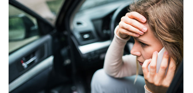Woman talking on the phone holding her head after an auto accident