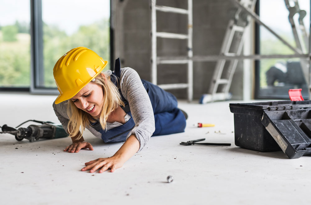 construction woman in hard hat on floor after accident