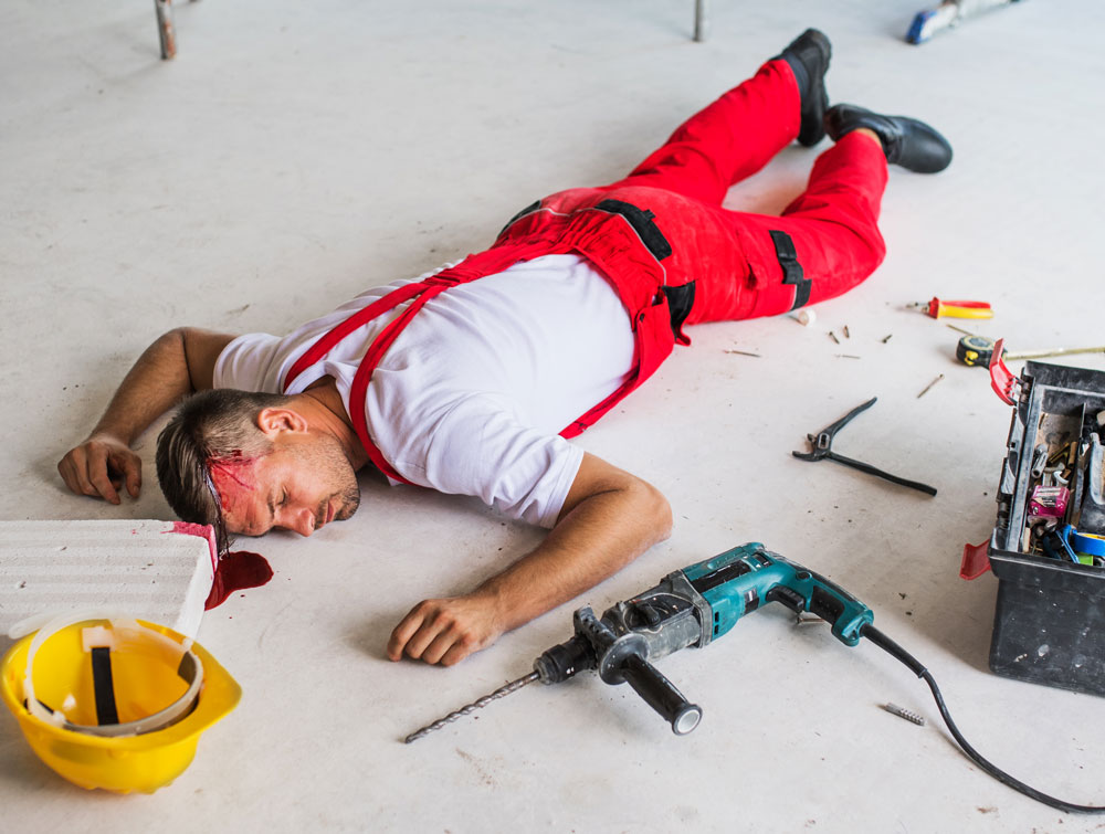 male worker lying on floor after suffering a head injury, bleeding from his head and unconscious