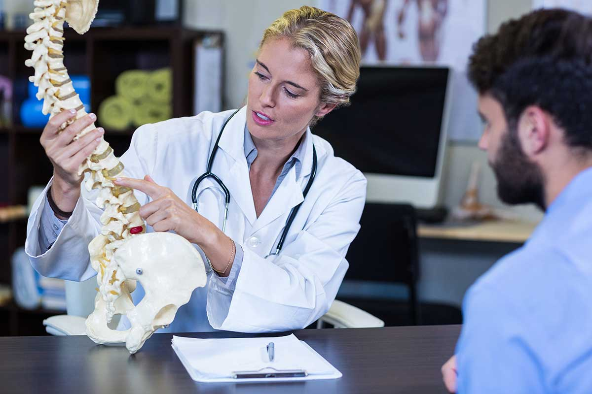 doctor explaining spine model to a patient