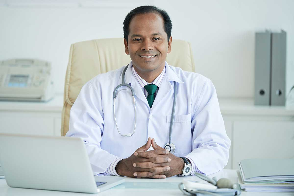 male doctor with stethoscope smiling sitting at desk