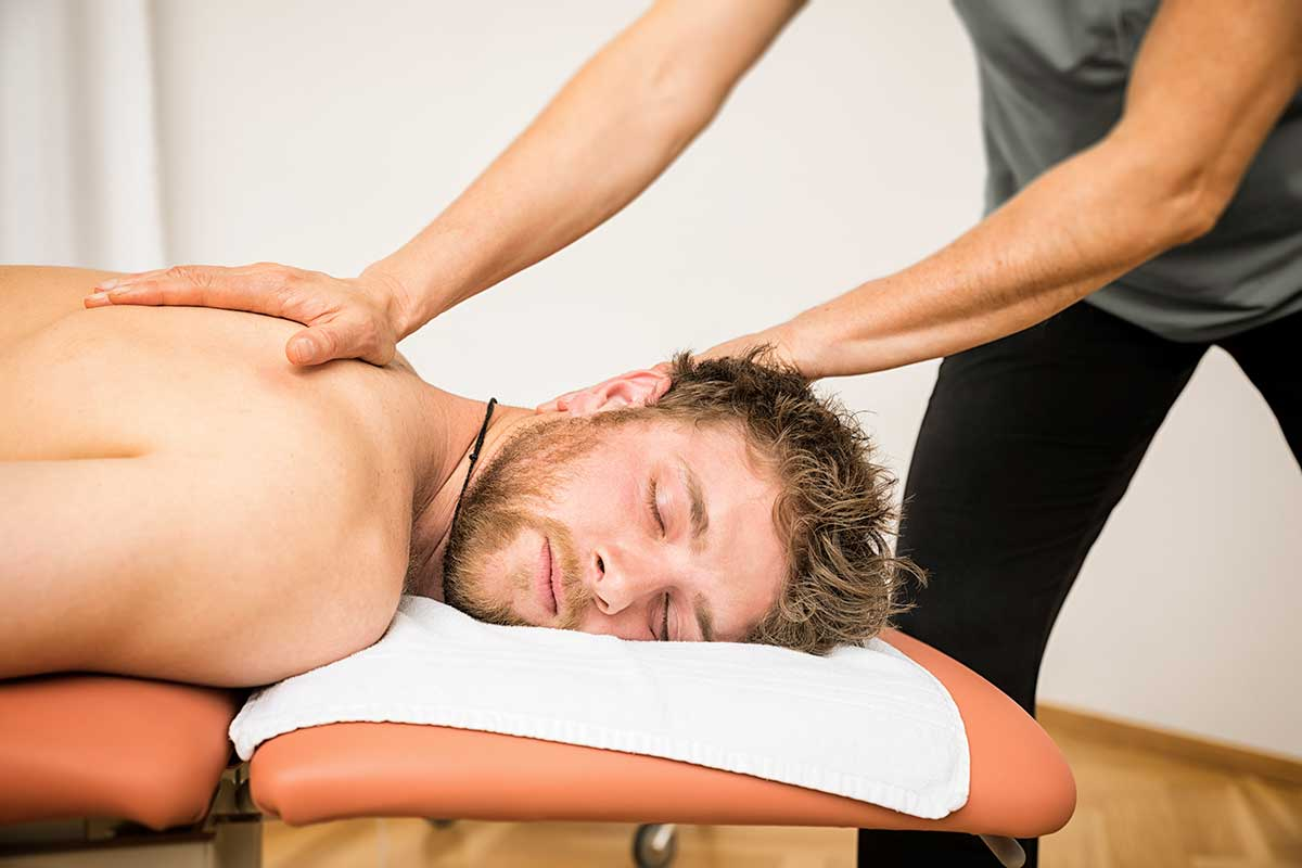 man lying on massage table receiving chiropractic care