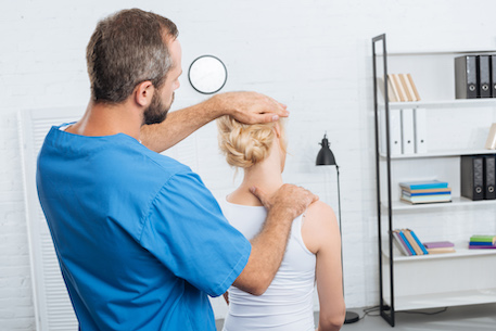 chiropractor stretching neck of woman during appointment in hospital