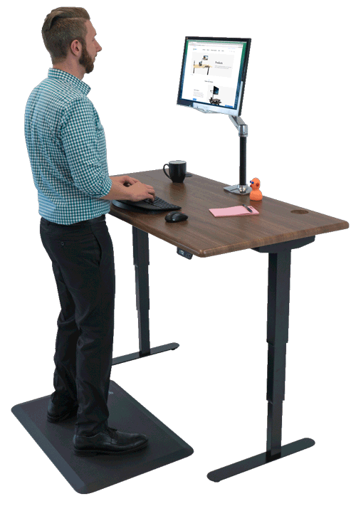 man standing at adjustable standing desk with computer and monitor
