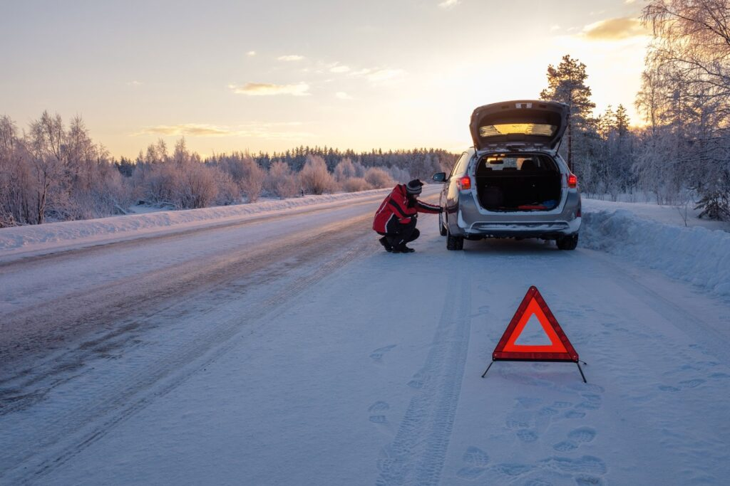 car on side of snowy road with a warning reflector set up