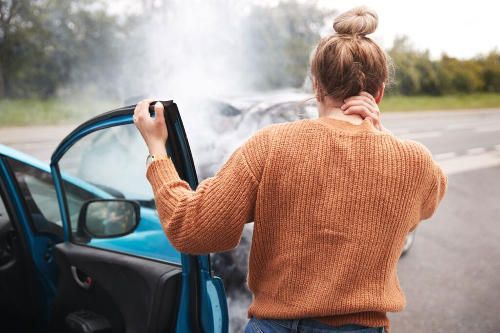 woman holding her neck after auto accident