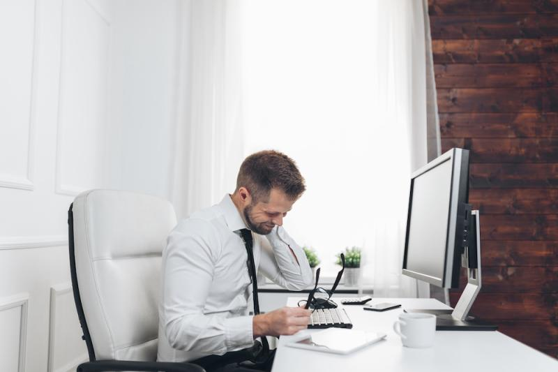 man sitting in front of a computer in the office
