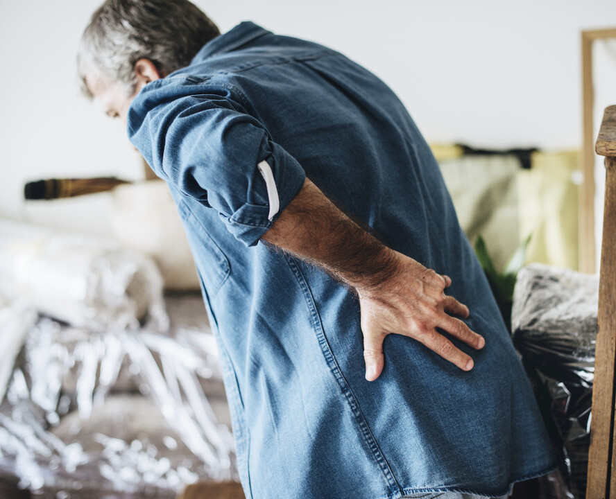 man clutching his back in pain