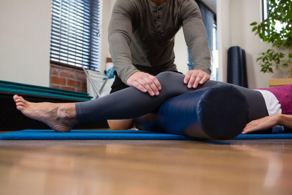 chiropractor massaging a woman's leg