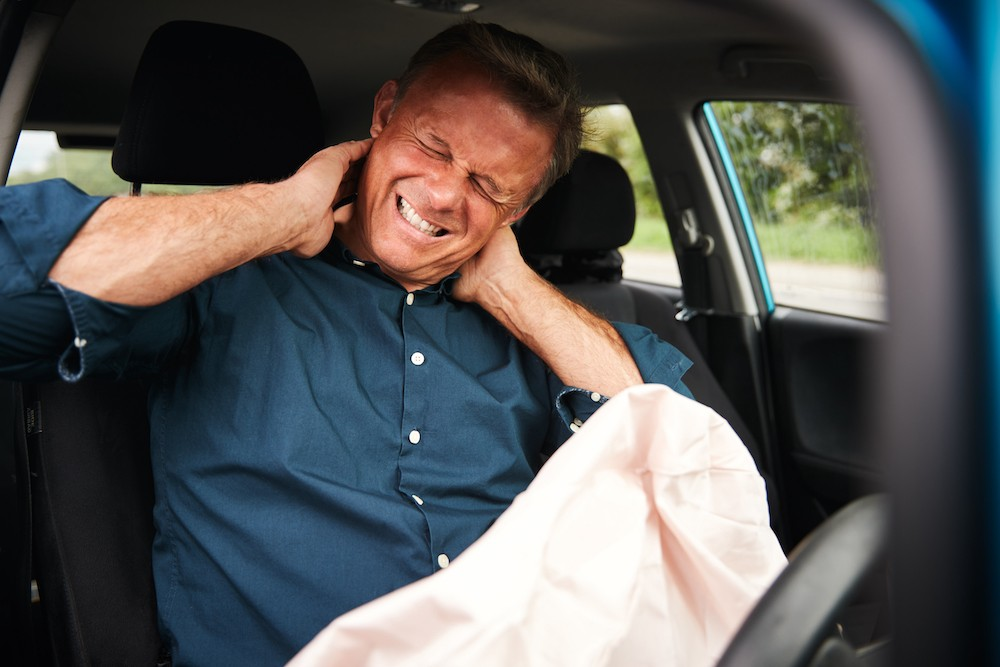 man in car holding his neck in pain