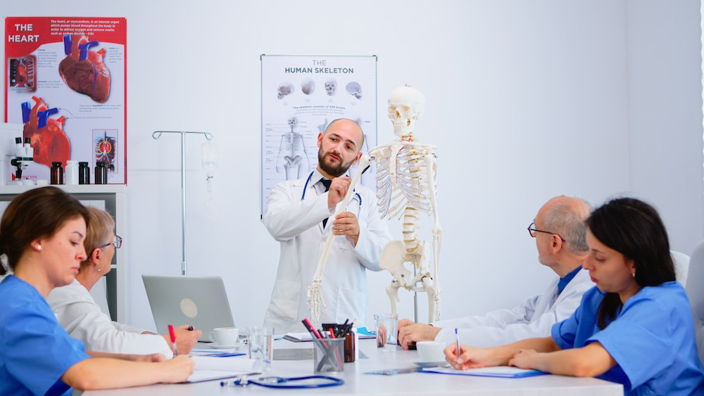 Doctor in lab coat with a model skeleton is instructing four colleagues sitting at a table