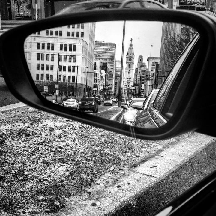 car side mirror reflecting downtown Philadelphia