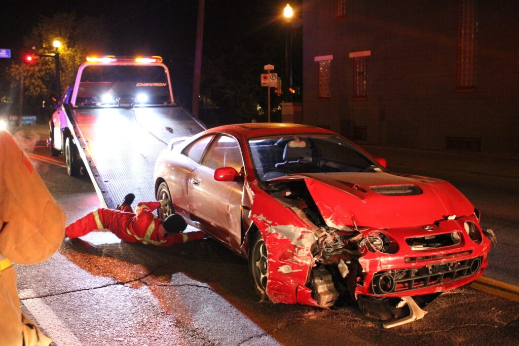 crashed red car being loaded onto a tow truck