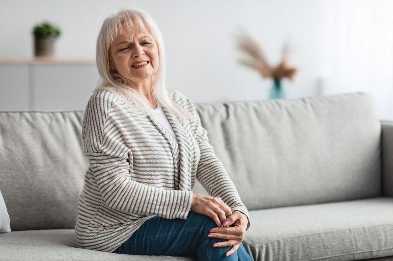 woman sitting on sofa wincing in pain