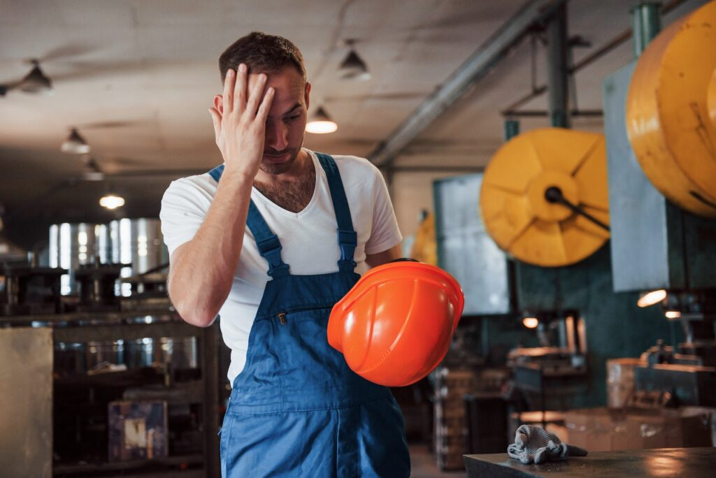 man in coveralls holds his aching head