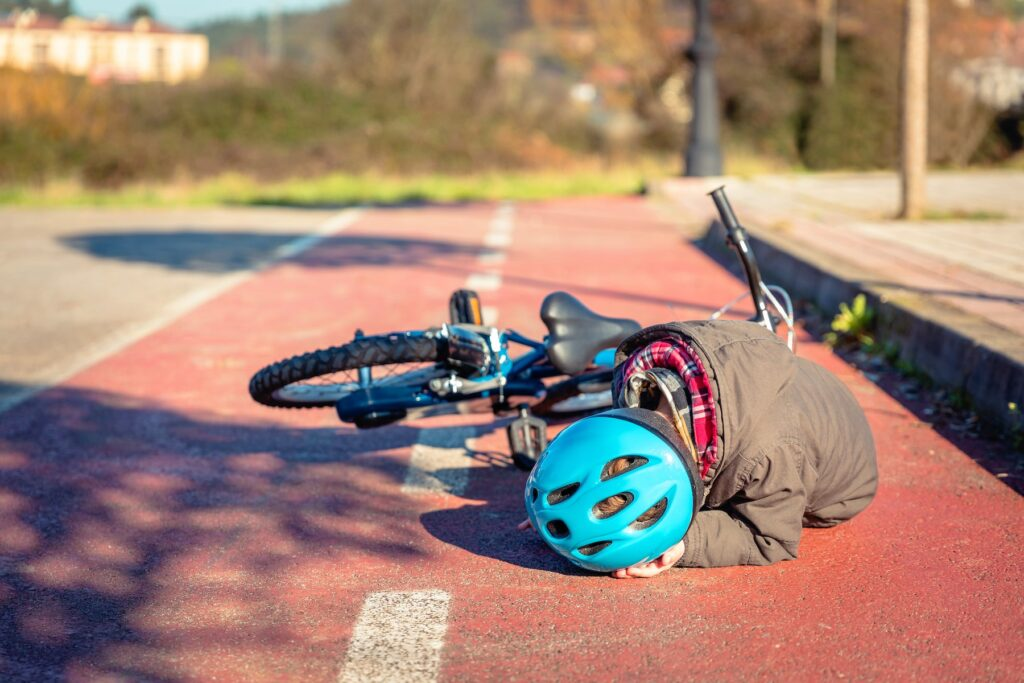 child lying on pavement after falling off bicycle