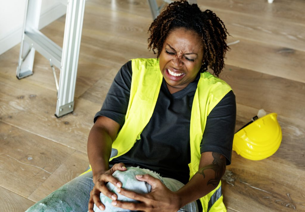 African American woman on the floor grabbing her knee in pain after a workplace accident