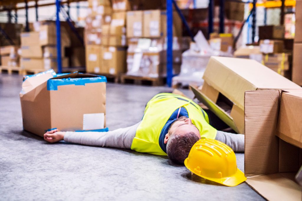 Worker in stock room lays on the floor unconscious after boxes fell on him.